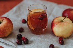 Bistri sok od jabuke u čaši oko kojeg se nalazi nekoliko jabuka
