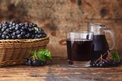 Sok od aronije u malom bokaliću i u čaši, te plod aronija ubran u maloj košarici
