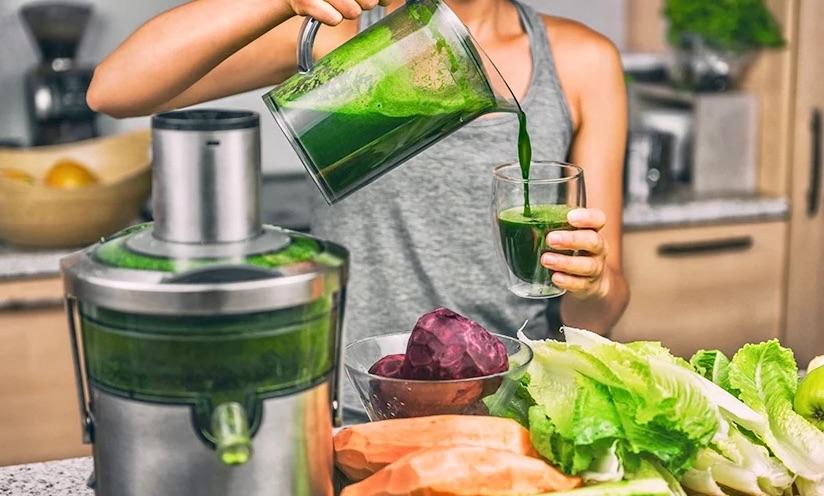 Čišćenje organizma prirodnim sokovima. Na slici se vidi blender u kojem je zeleni sok. Žena koja sipa zeleni sok iz bokala u čašu i puno povrća raznih boja na stolu.